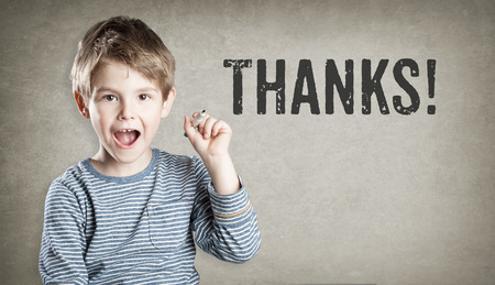 Boy saying Thanks on grunge background, writing, amazed, copy space