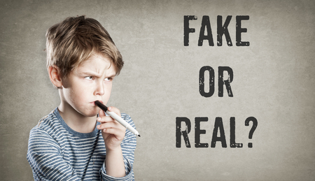 Fake or real, Boy considering the question, on grunge background, writing and thinking, copy space Stock Photo - 70296415