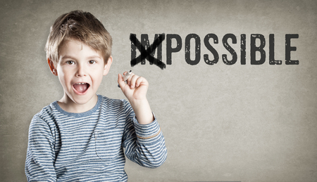 think through: Boy tunr impossible into posisble, on grunge background, writing, amazed, copy space