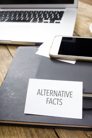 Card saying Alternative Facts on note pad at desktop in office with laptop, tablet computer and phone.