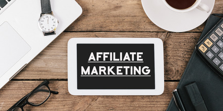 affiliate marketing: Words Affiliate Marketing on phone, Office desk with electronic devices, computer and paper, wood table from above, concept image for blog title or header image. Stock Photo