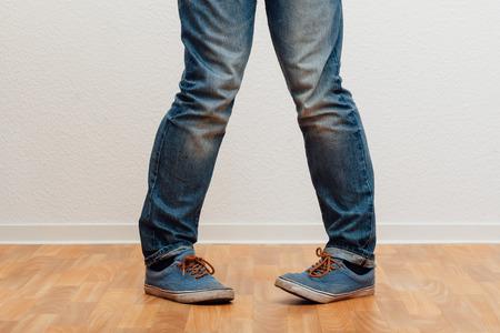 Bottom half closeup to man standing with knock-knees, people indoors studio shot. Stock fotó