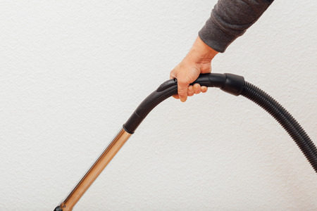 Male hand holding grip of vacuum cleaner in action, people indoors studio shot.