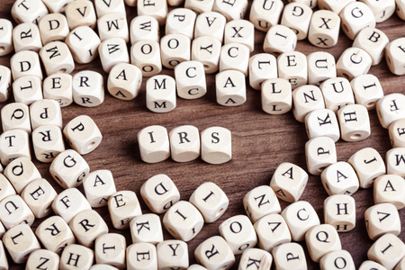 irs: Word IRS in letters on cube dices on table.