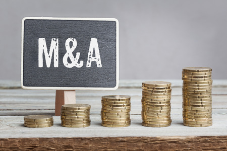 mergers: Chalkboardblackboard-sign, reading Mergers and Acquisitions in white font, five coin stacks of eurocents on grey background, increasing in size from left to right, increasing wealth, concept image with money