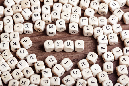 Word IFRS in letters on cube dices on table.