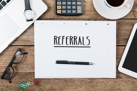 referidos: word referrals on notebook, Office desk with electronic devices, computer and paper, wood table from above, concept image for blog title or header image. Foto de archivo