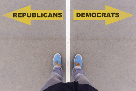 footsie: Republicans vs Democrats text on yellow arrows on asphalt ground, feet and shoes on floor, personal perspective footsie concept Stock Photo