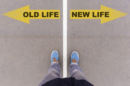 Old life vs New life text on yellow arrows on asphalt ground, feet and shoes on floor, personal perspective footsie concept