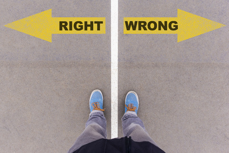 Right vs Wrong text on yellow arrows on asphalt ground, feet and shoes on floor, personal perspective footsie concept