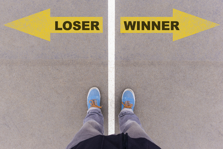 footsie: Loser vs Winner text on yellow arrows on asphalt ground, feet and shoes on floor, personal perspective footsie concept Stock Photo