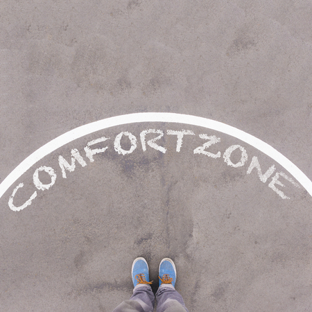 footsie: Comfort zone text on asphalt ground, feet and shoes on floor, personal perspective footsie concept Stock Photo