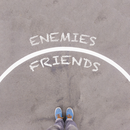 footsie: Enemies vs Friends text on asphalt ground, feet and shoes on floor, personal perspective footsie concept
