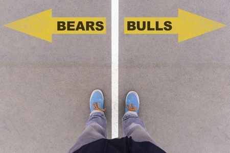 footsie: Bears and Bulls text on yellow arrows on asphalt ground, feet and shoes on floor, personal perspective footsie concept