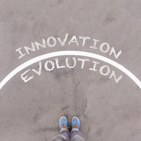 footsie: Evolution vs Innovation text on asphalt ground, feet and shoes on floor, personal perspective footsie concept Stock Photo