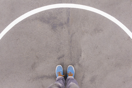 footsie: Semi circle arch on asphalt ground, feet and shoes on floor, personal perspective footsie concept Stock Photo