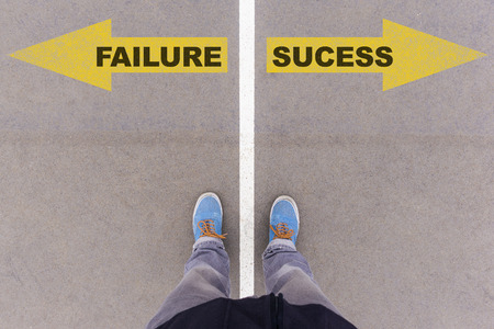 footsie: Failure vs success text on yellow arrows on asphalt ground, feet and shoes on floor, personal perspective footsie concept Stock Photo