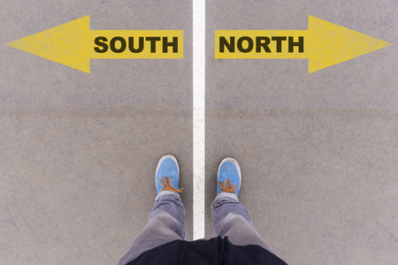 footsie: South vs North text on yellow arrows on asphalt ground, feet and shoes on floor, personal perspective footsie concept Stock Photo