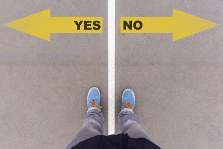 footsie: Yes or No text on yellow arrows on asphalt ground, feet and shoes on floor, personal perspective footsie concept Stock Photo