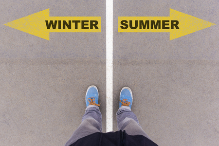 footsie: Winter and Summer text on yellow arrows on asphalt ground, feet and shoes on floor, personal perspective footsie concept Stock Photo