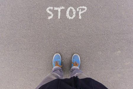 footsie: Stop text on asphalt ground, feet and shoes on floor, personal perspective footsie concept