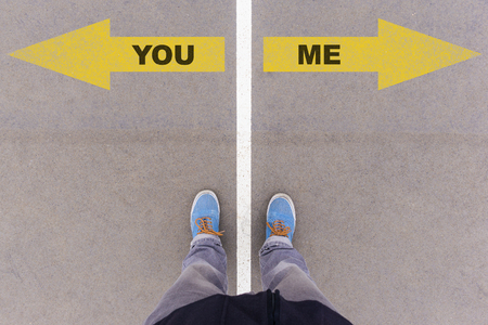 footsie: You or Me text on yellow arrows on asphalt ground, feet and shoes on floor, personal perspective footsie concept Stock Photo