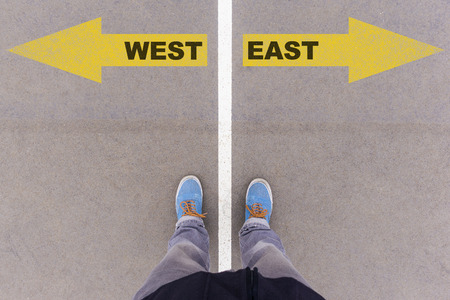 footsie: West and East text on yellow arrows on asphalt ground, feet and shoes on floor, personal perspective footsie concept