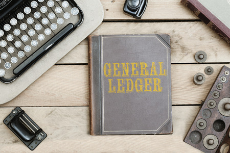 General Ledger text on cover of old book on office desk with vintage type writer machine from 1920s and other obsolete office items.