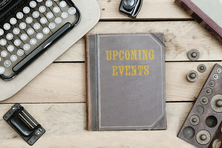 upcoming: Upcoming Events text on cover of old book on office desk with vintage type writer machine from 1920s and other obsolete office items. Stock Photo