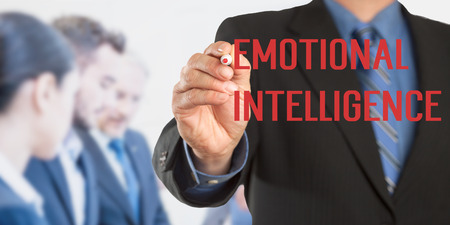 Emotional Intelligence, Male hand in business wear holding a thick pen writing, with office team blurred in background, digital composing. Stock Photo