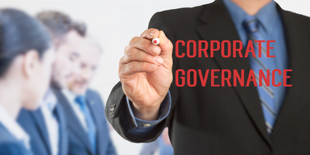 gobierno corporativo: Corporate Governance, Male hand in business wear holding a thick pen writing, with office team blurred in background, digital composing.