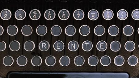 Word Rente (German for Pension) on vintage type writer letter keys from 1920s close up, digital composing.