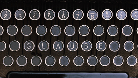 glaube: Word Glaube (German for Belief) on vintage type writer letter keys from 1920s close up, digital composing.