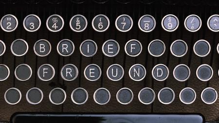 pal: Word Brieffreund (German for Pen Pal) on vintage type writer letter keys from 1920s close up, digital composing.