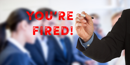 You Are Fired, Male hand in business wear holding a thick pen, writing on an imaginary screen at the camera, business team in background, digital composing.