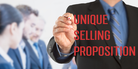 Unique Selling Proposition USP, Male hand in business wear holding a thick pen writing, with office team blurred in background, digital composing. Stock Photo