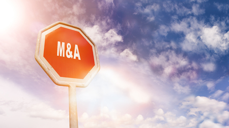 Mergers and Acquisitions on red traffic road stop sign in front of blue sky with clouds and friendly sun beams, digital composing with light leaks and flares
