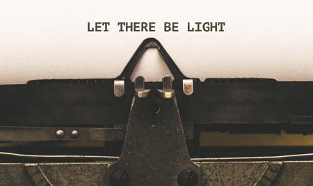 Let there be light, Text on paper in Vintage type writer machine from 1920s closeup with paper Zdjęcie Seryjne