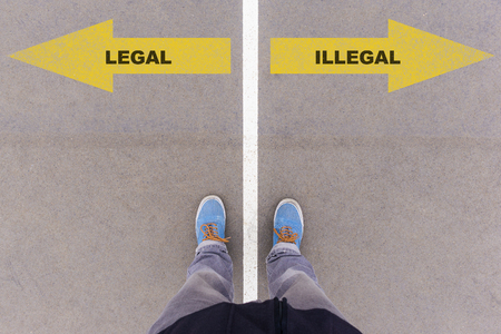 antipode: Legal or Illegal choice; text on asphalt ground, feet and shoes on floor, personal perspective footsie concept