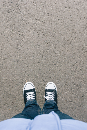 Pair of legs and shoes on asphalt ground, high angle footsie or flortrait, personal pespective from above. Imagens