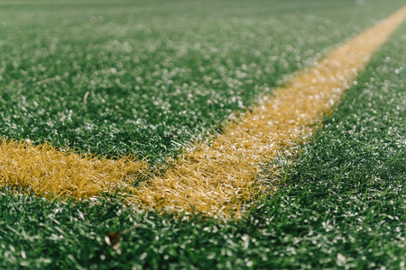 Yellow side line corner on green artificial grass on turf sports field from above, closeup with details and shallow depth of field in opposing sun light