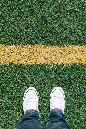 footsie: Artificial turf grass with yellow side line on sports field with two shoes, personal perspective from above, footsie or flortrait
