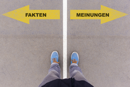 Fakten oder Meinungen (German for facts or opinions) direction sign text on asphalt ground, feet and shoes on floor, personal perspective footsie concept