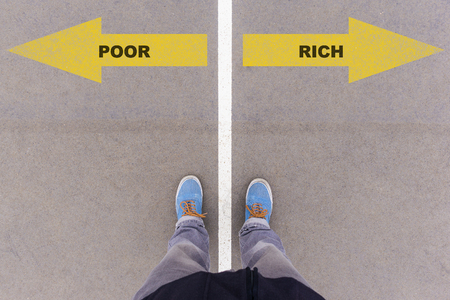 antipode: Poor or rich choice; text on asphalt ground, feet and shoes on floor, personal perspective footsie concept