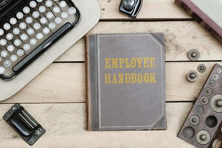 Werknemershandboektekst op dekking van oud boek op bureau met uitstekende typeschrijvermachine van jaren 20 en andere verouderde bureaupunten.