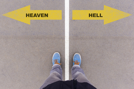 antipode: Heaven or hello direction signs, text on asphalt ground, feet and shoes on floor, personal perspective footsie concept Stock Photo