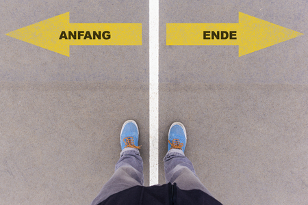 ende: Anfang und Ende (German for beginning and end) direction sign text on asphalt ground, feet and shoes on floor, personal perspective footsie concept