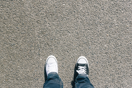 Pair of legs, different black and white shoes on asphalt ground, high angle footsie or flortrait, personal pespective from above.