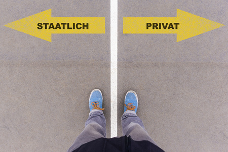 privat: Staatlich  Privat (German for public and private) direction sign text on asphalt ground, feet and shoes on floor, personal perspective footsie concept