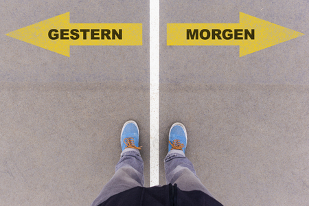 Gestern  Morgen (German for yesterdaytomorrow) direction sign text on asphalt ground, feet and shoes on floor, personal perspective footsie concept